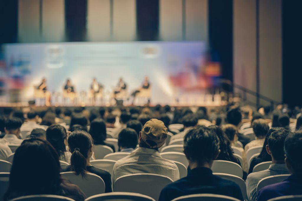 Czym kierować się przy wyborze sali konferencyjnej? Widok osób na konferencji firmowej.