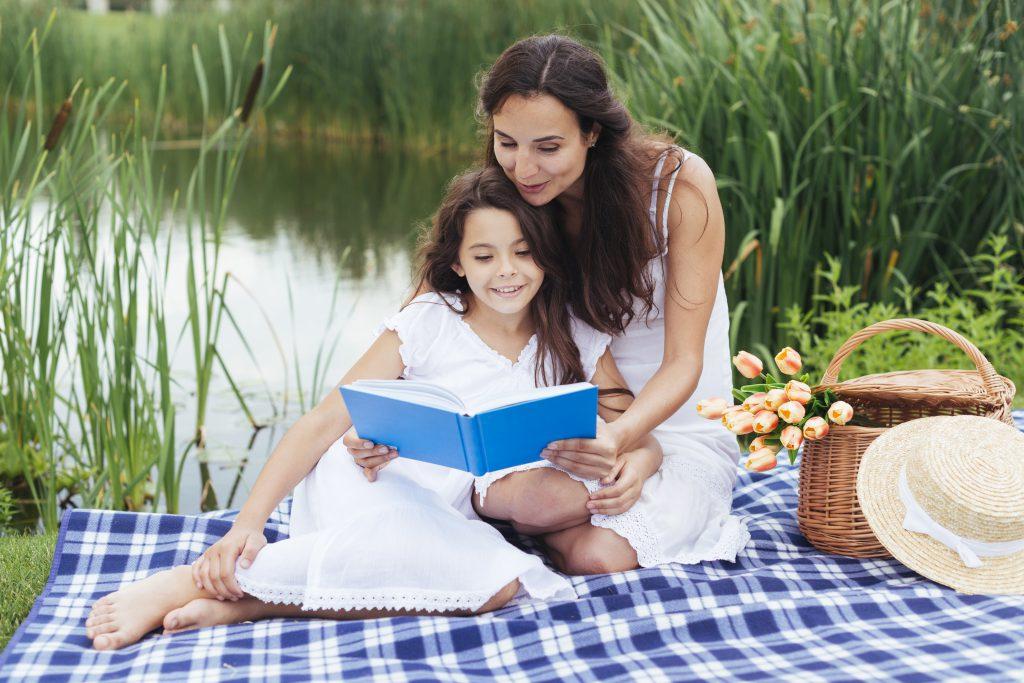 Wakacje z dziećmi na Mazurach. Mama czyta książkę swojej córeczce na kocu nad jeziorem